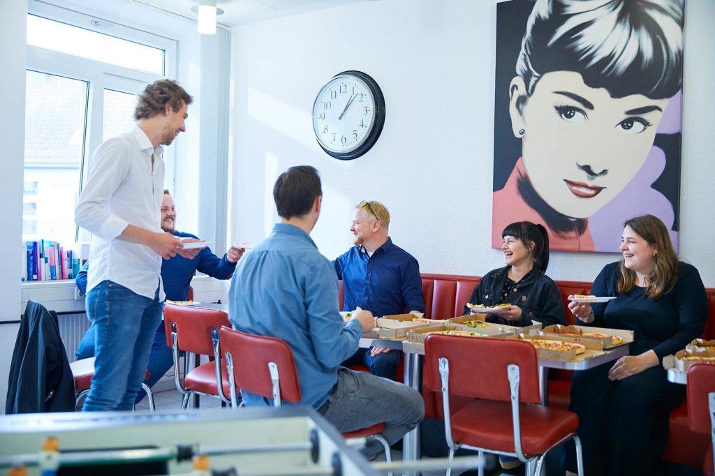 Mitarbeiter essen Pizza in der Küche