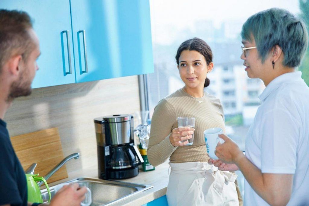 Drei Mitarbeiter halten Smalltalk in der Küche