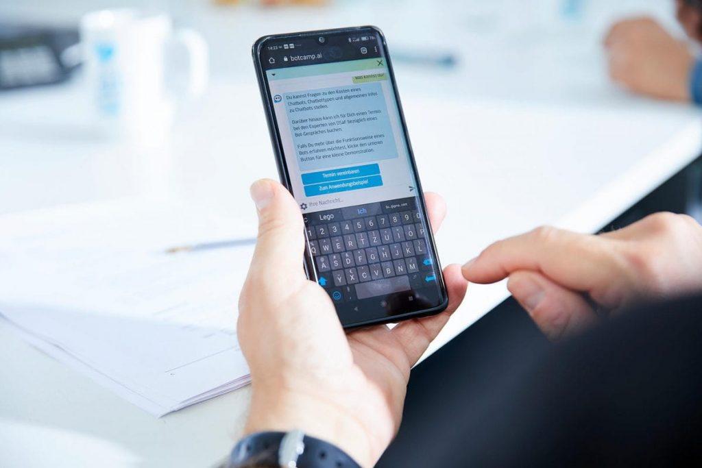 mitarbeiter nutzt handy für bot chat